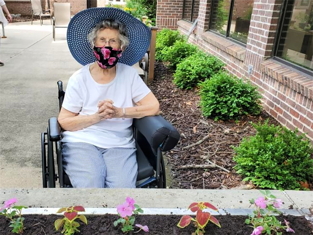 Older adult female outdoors gardening in the summer with a sunhat and face mask on