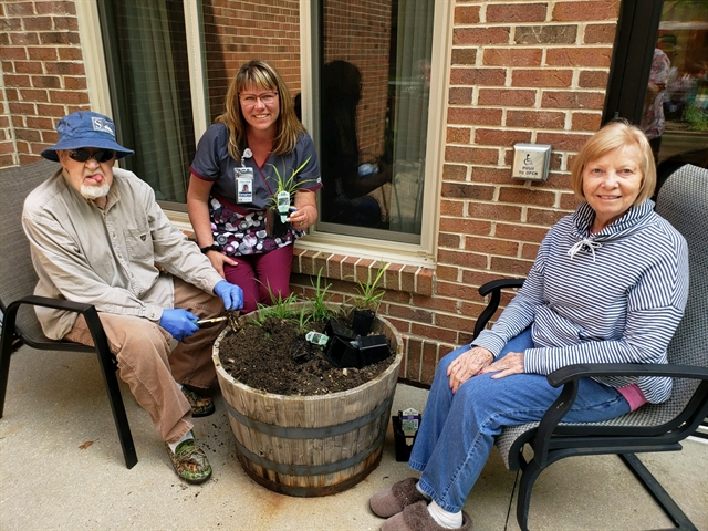 Specially trained Memory Care caregiver enjoys gardening outdoors with older adult residents