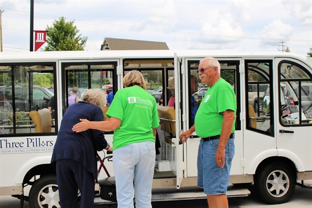 Volunteers at a Life Plan community help guests on the shuttle