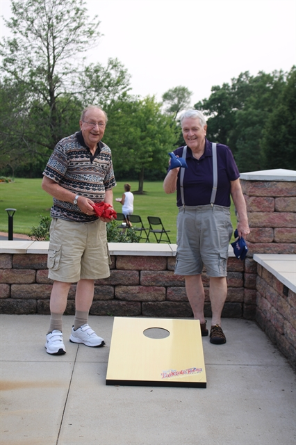 Male residents at Three Pillars enjoy playing bags outdoors together for social and physical wellness.