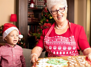 Grandmother and grandchild baking Christmas cookies - on a tray