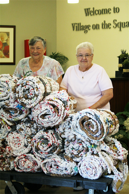 Residents at Three Pillars, smiling while making sleeping mats out of plastic shopping bags