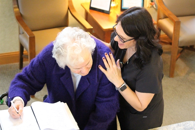 Nurse at senior community assisted living interacts with senior resident