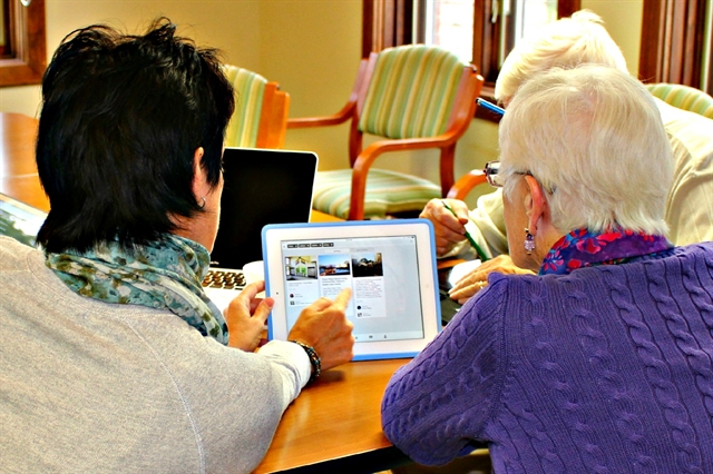 Older adult and daughter looking at information on an iPad screen, researching senior living communities and assisted living