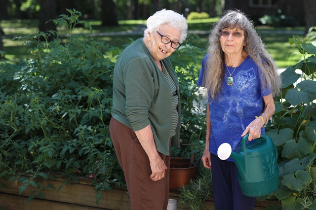 Older adult women enjoying the outdoors in a secure patio area at Three Pillars' Memory Care