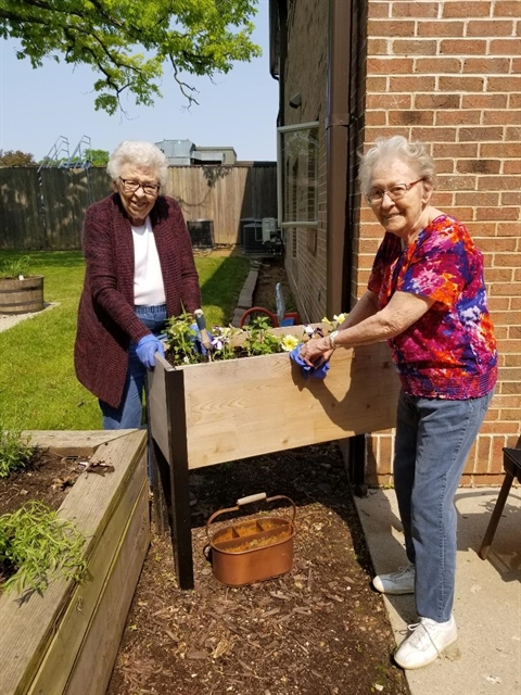 older adult senior women gardening outdoors at memory care