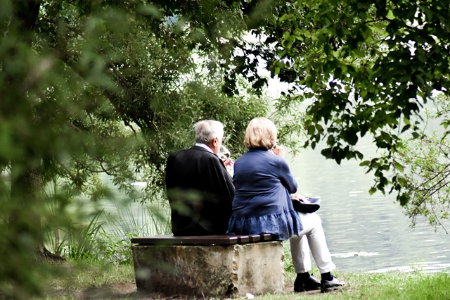 Older adult couple on a bench by the lake