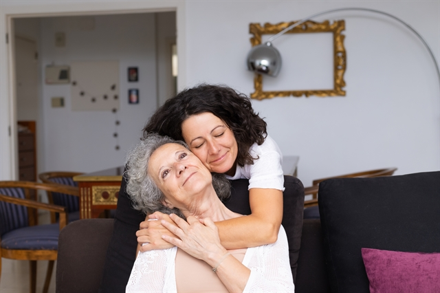Adult daughter smiling hugging older adult mother