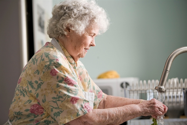 Older adult senior woman doing housework at the sink