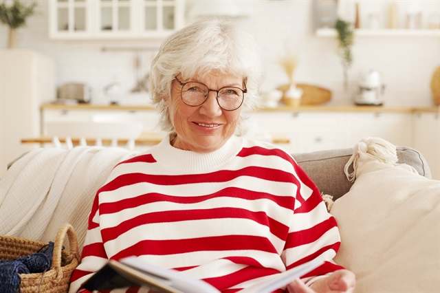 Older adult senior woman reading on her couch