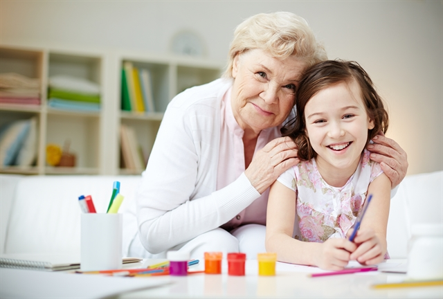 Grandmother and Grandchild girl painting together, doing arts and crafts smiling